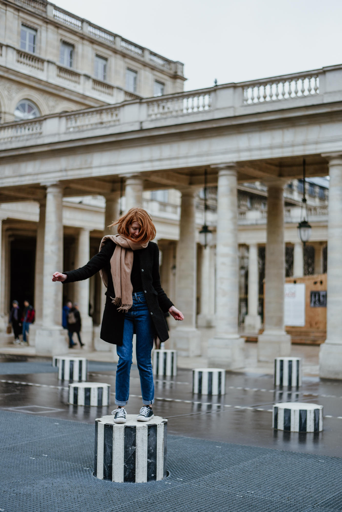 Girl with Les Deux Plateaux Colonnes de Buren at Palais Royal in Paris