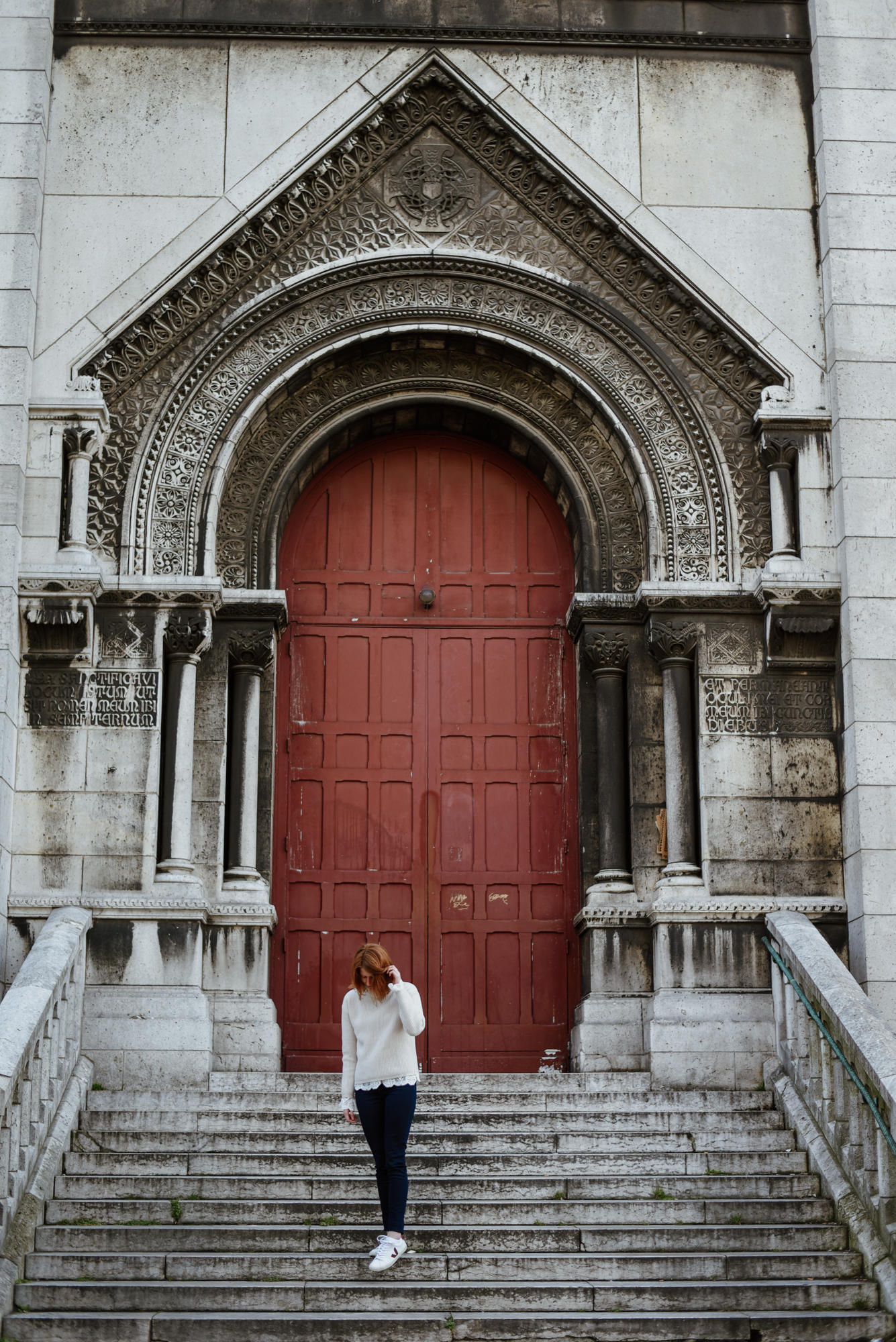 girl in front of door from sacre coeur in paris