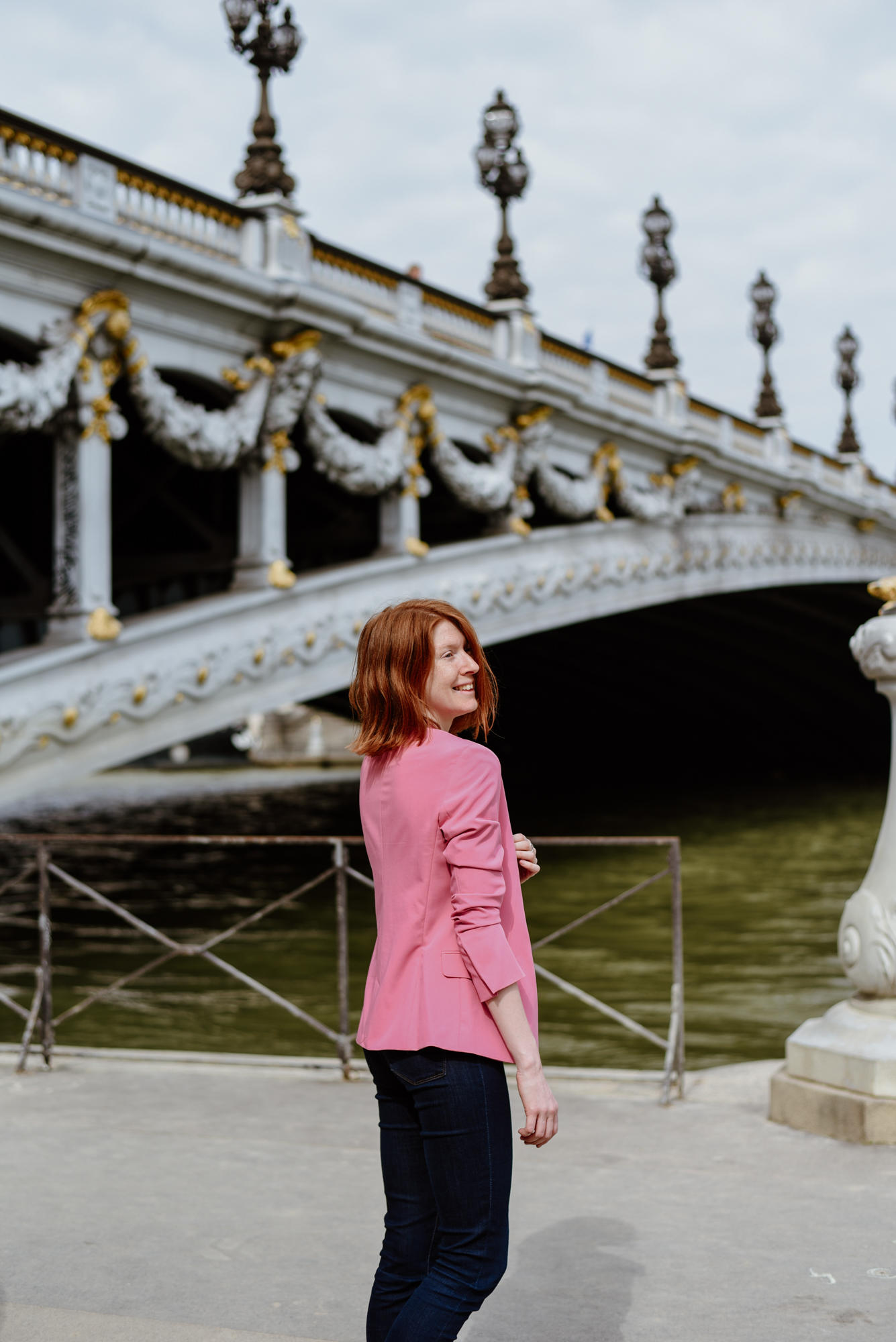 girl with pink jacket next to Pont Alexandre III in Paris