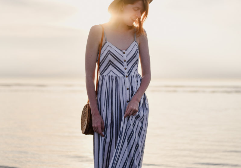 Girl in striped sundress walking in the sea during sunset