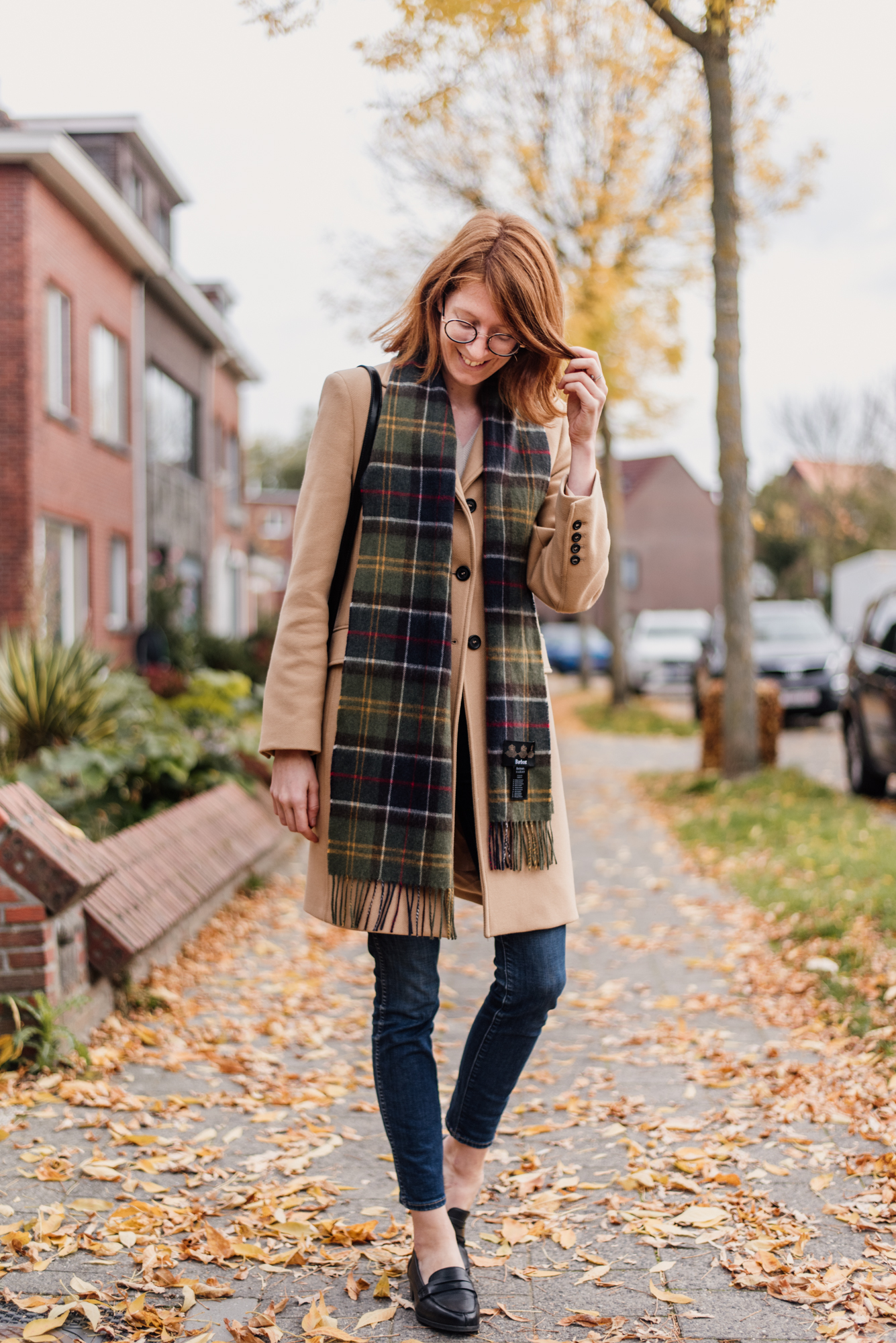 Woman wearing a camel colored coat from Zara and a plaid scarf from Barbour in an outfit for autumn