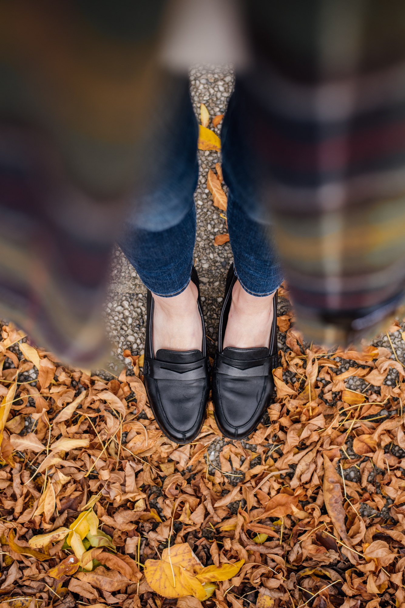 Woman wearing black loafers from clarks while standing on a pile of yellow fallen leaves