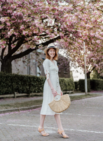 Girl in white dress and with a straw bag posing in front of cherry blossoms